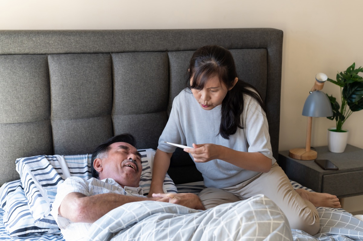 Senior man suffering from fever and stomach pain. The man pressing on stomach with painful expression. Wife checking body temperature of her ill husband on bed.