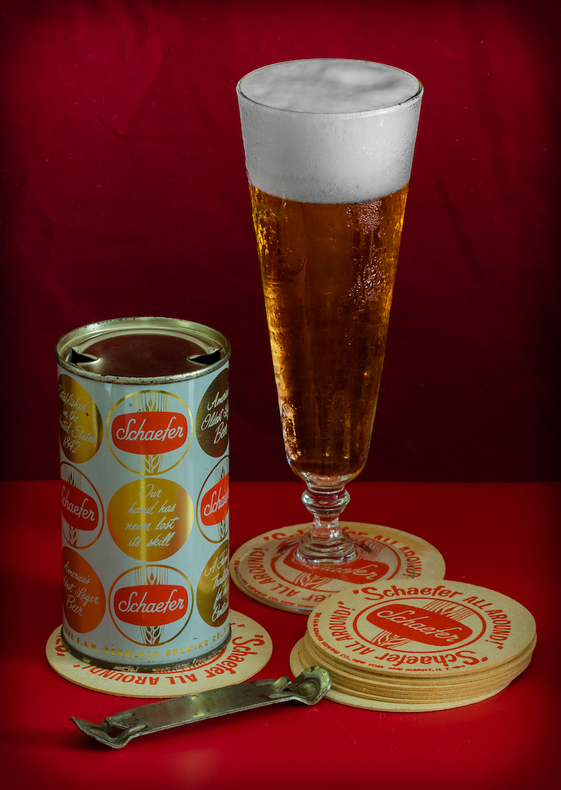 Flat top Schaefer beer can with a pilsner glass of beer, can opener and Schaefer all around coasters on a red table and red background