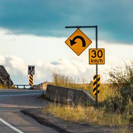 curve in highway with yellow warning sign
