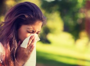woman sneezing into a tissue outside