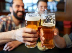 men in a bar toasting with glasses of beer