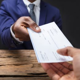 Man in suit handing a paycheck to someone