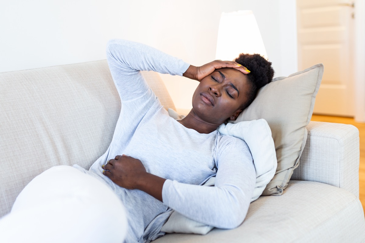 woman suffering from stomachache on sofa at home