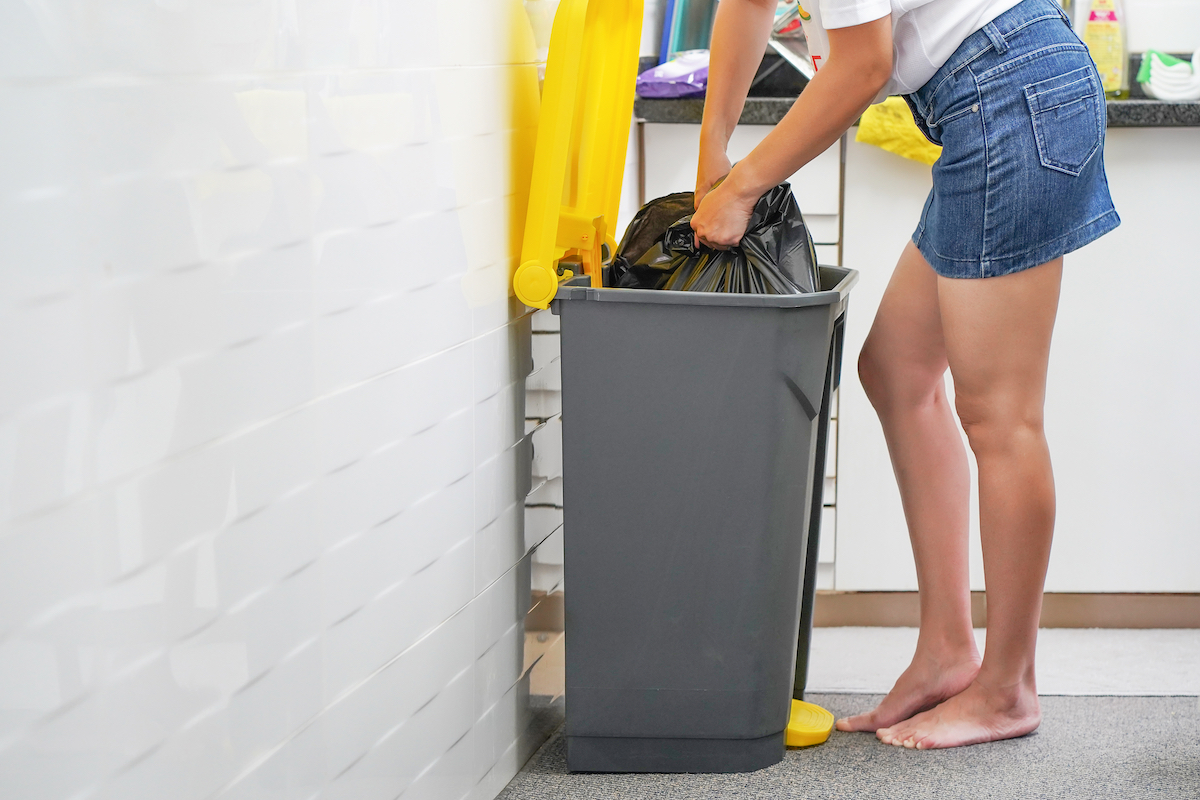 Woman putting food in black trash bag in the kitchen.