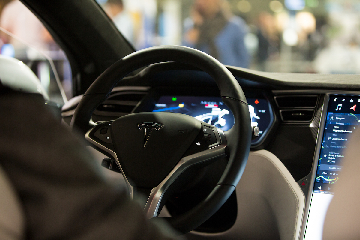The interior of a Tesla Model X electric car with large touch screen dashboard, wheel.