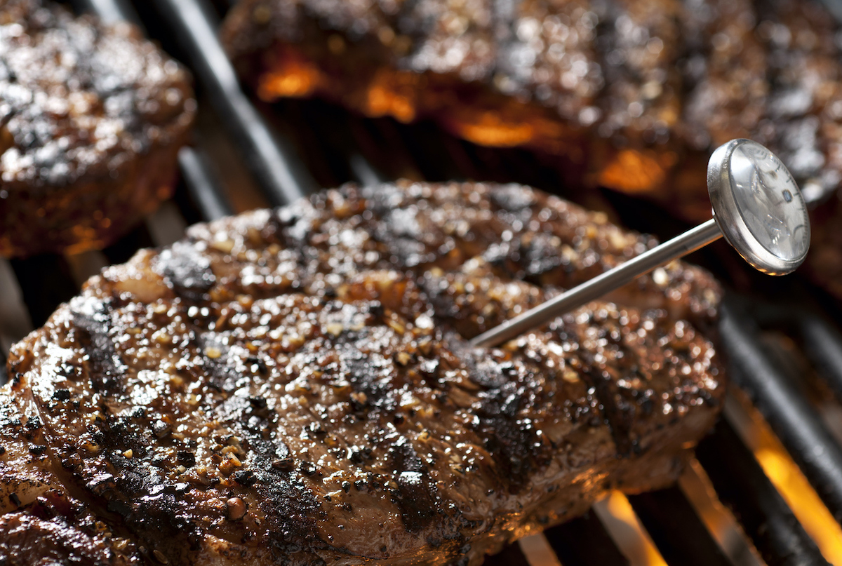 Steaks on the grill with thermometer to check internal temperature