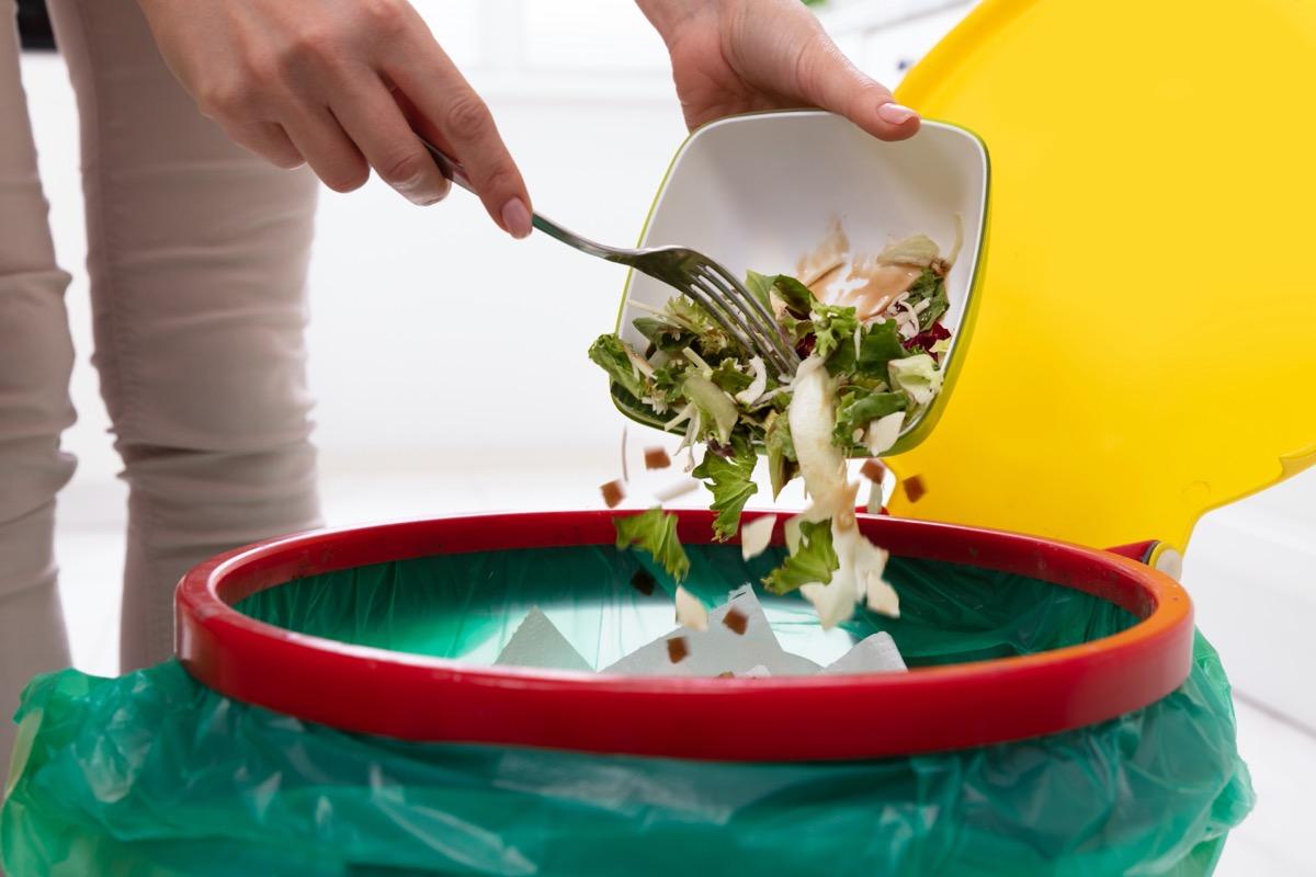 woman throwing away salad