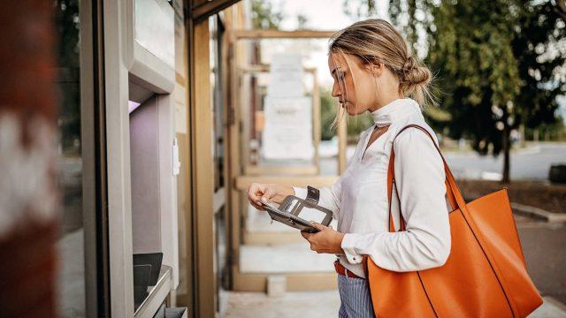 Women using ATM machine to withdraw money