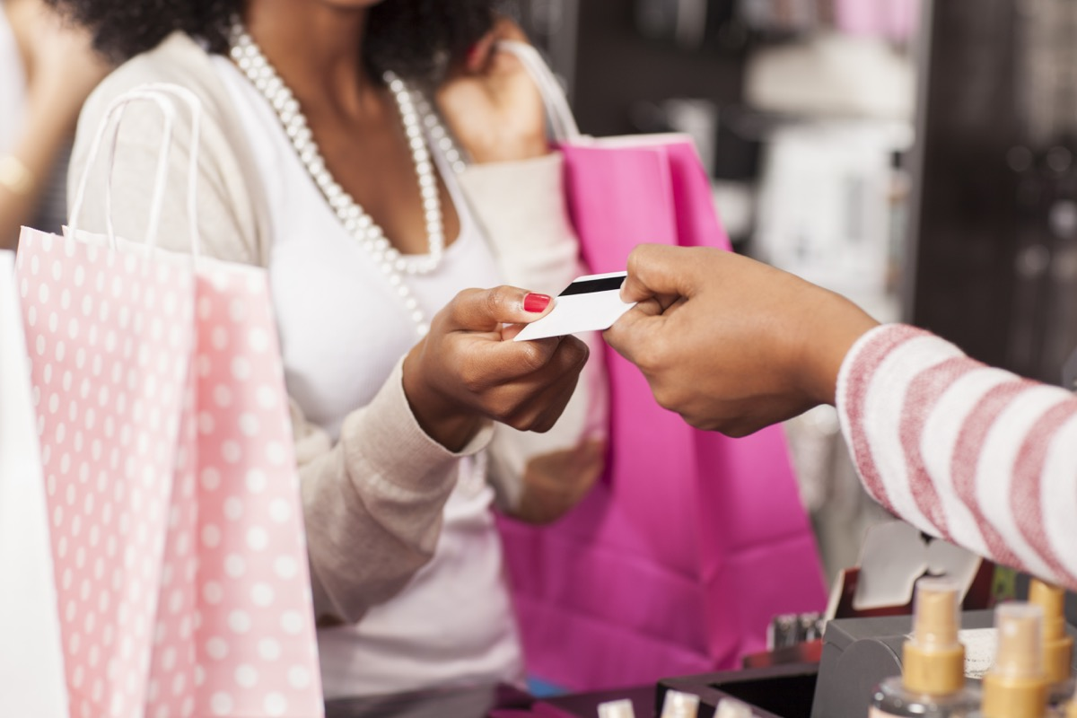 Unrecognised woman shopping, holding paper bags and paying by credit card.