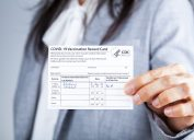 Woman is showing her CDC issued COVID vaccination record card as a proof of immunization.