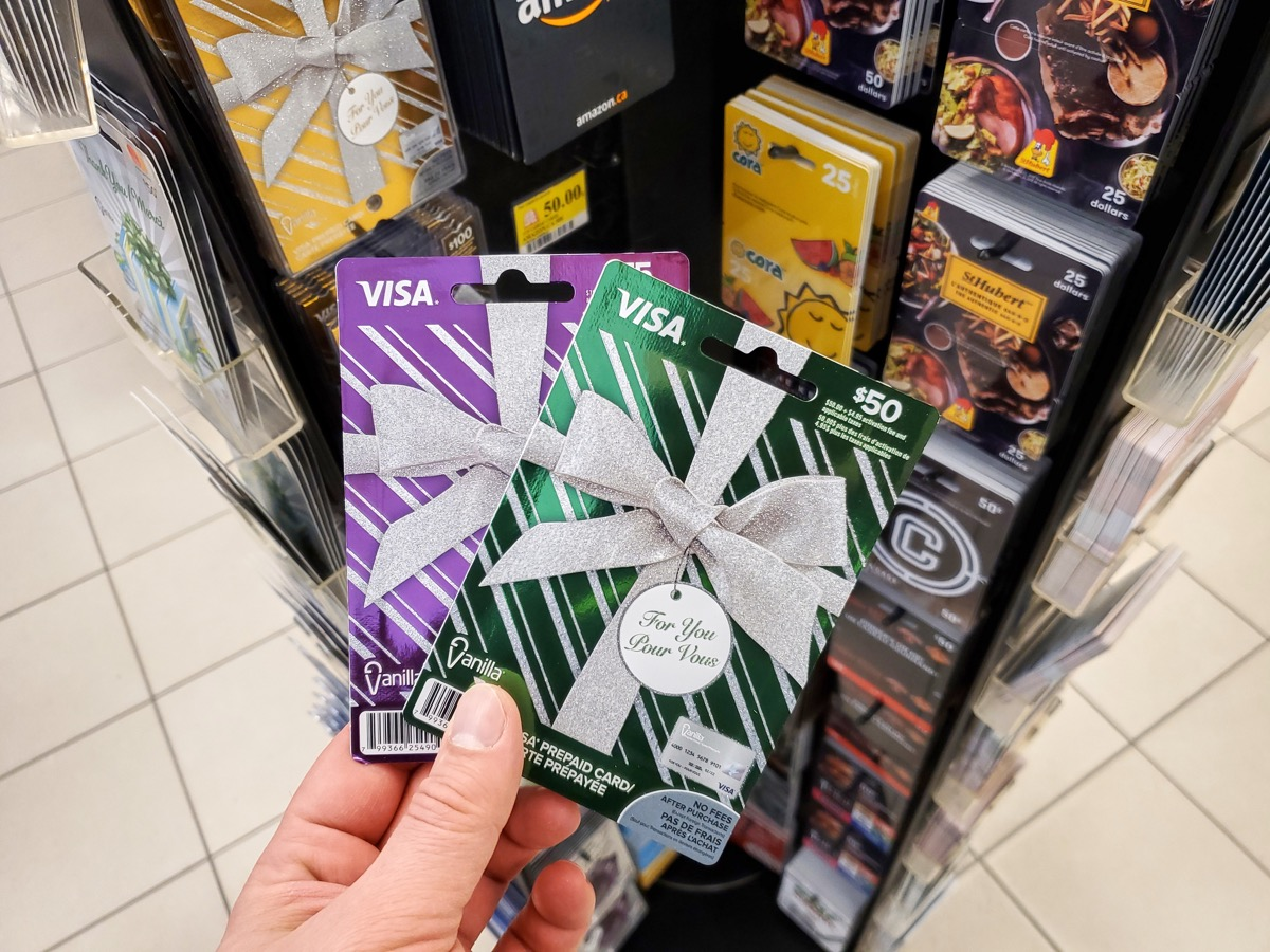 Montreal, Canada - March 22, 2020: Visa gift card in a hand over gift cards background. Visa is an American multinational financial services corporation headquartered in Foster City