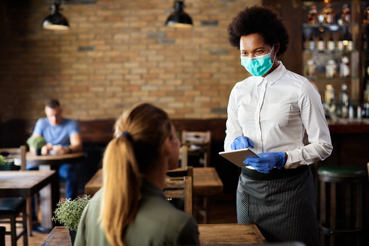 waitress wearing protective face mask while taking order from customer on a touchpad in a cafe.