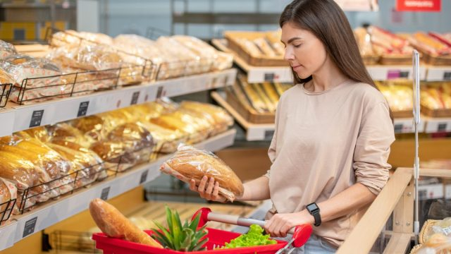 woman shopping for bread at supermarket