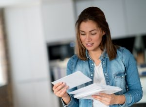A woman checking her mail in her home