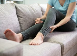young woman on couch massaging calf cramp