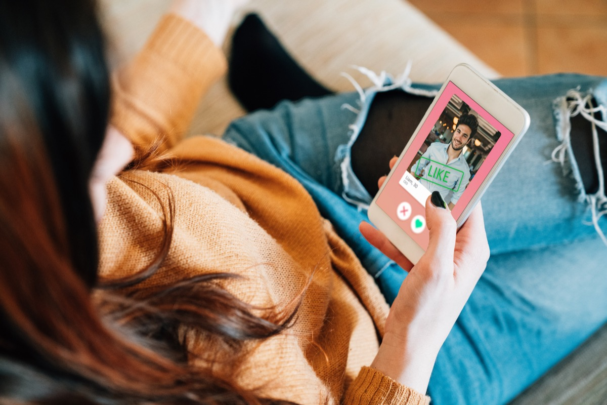 Young adult woman swiping on an online dating app. She's using her smart phone on the sofa at home.