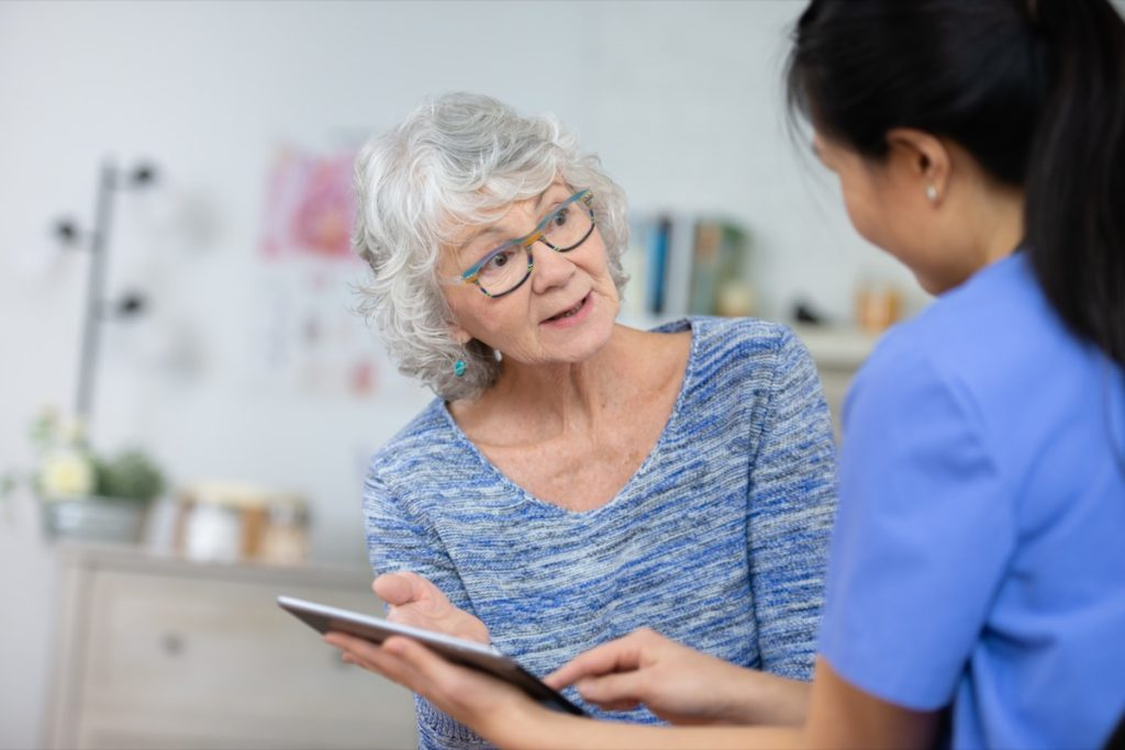A senior woman speaks to her doctor about her health. She looks at her doctor after she explained to her what she needs to be healthy. The doctor is holding a tablet.