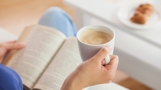 woman drinking coffee and reading