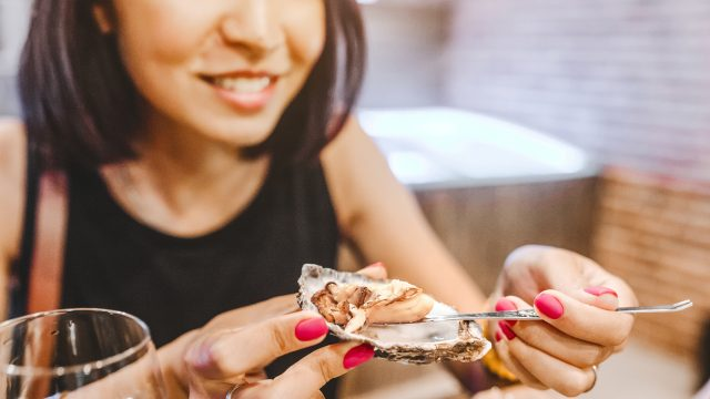 A woman about to eat an oyster from the shell in a restaurant