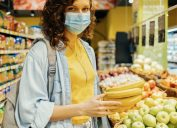 A young woman wearing a face mask while holding a bunch of bananas in a grocery store