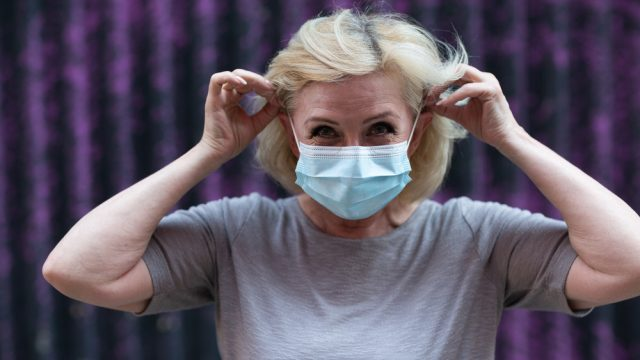A senior woman putting on a medical-grade face mask to protect herself from the Delta variant
