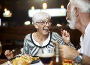 A senior woman feeding a senior man a bite of food during dinner at a restaurant