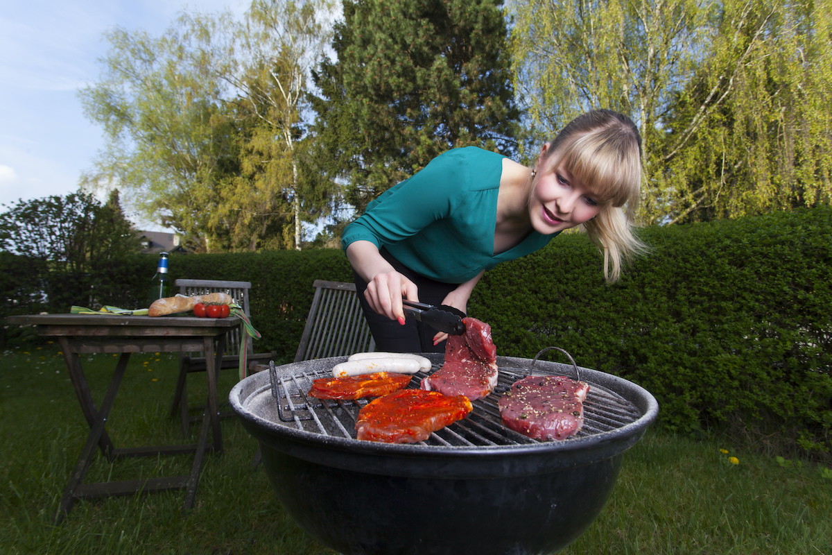 Woman cooking steak on barbecue