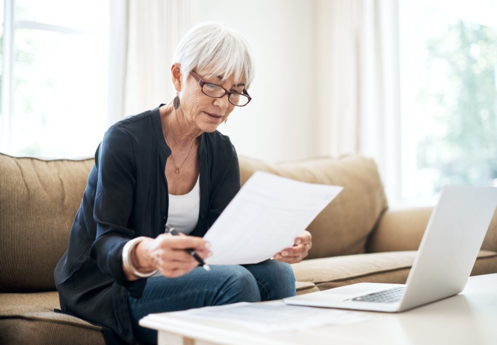 Cropped shot of a senior woman going through her finances while sitting on the sofa at home