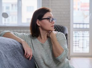 mature woman sitting on the floor at home, sad middle-aged woman alone experiencing health problems and personal troubles