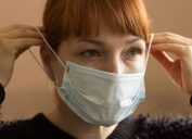 Closeup of a young woman putting on a protective face mask