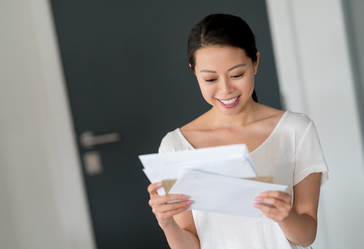 woman at home checking her mail and looking very happy - lifestyle concepts