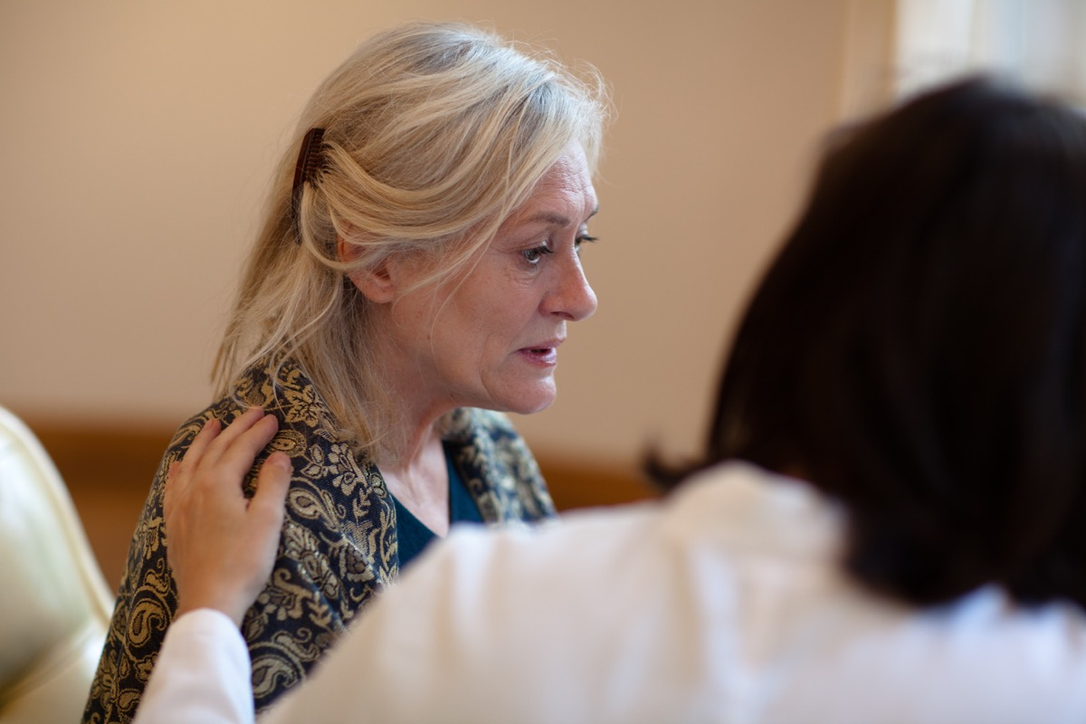 senior woman gets attention - hand on shoulder