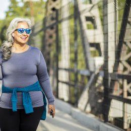 A senior woman walking across a bridge for exercise
