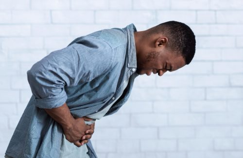 young man bending over with stomach pain