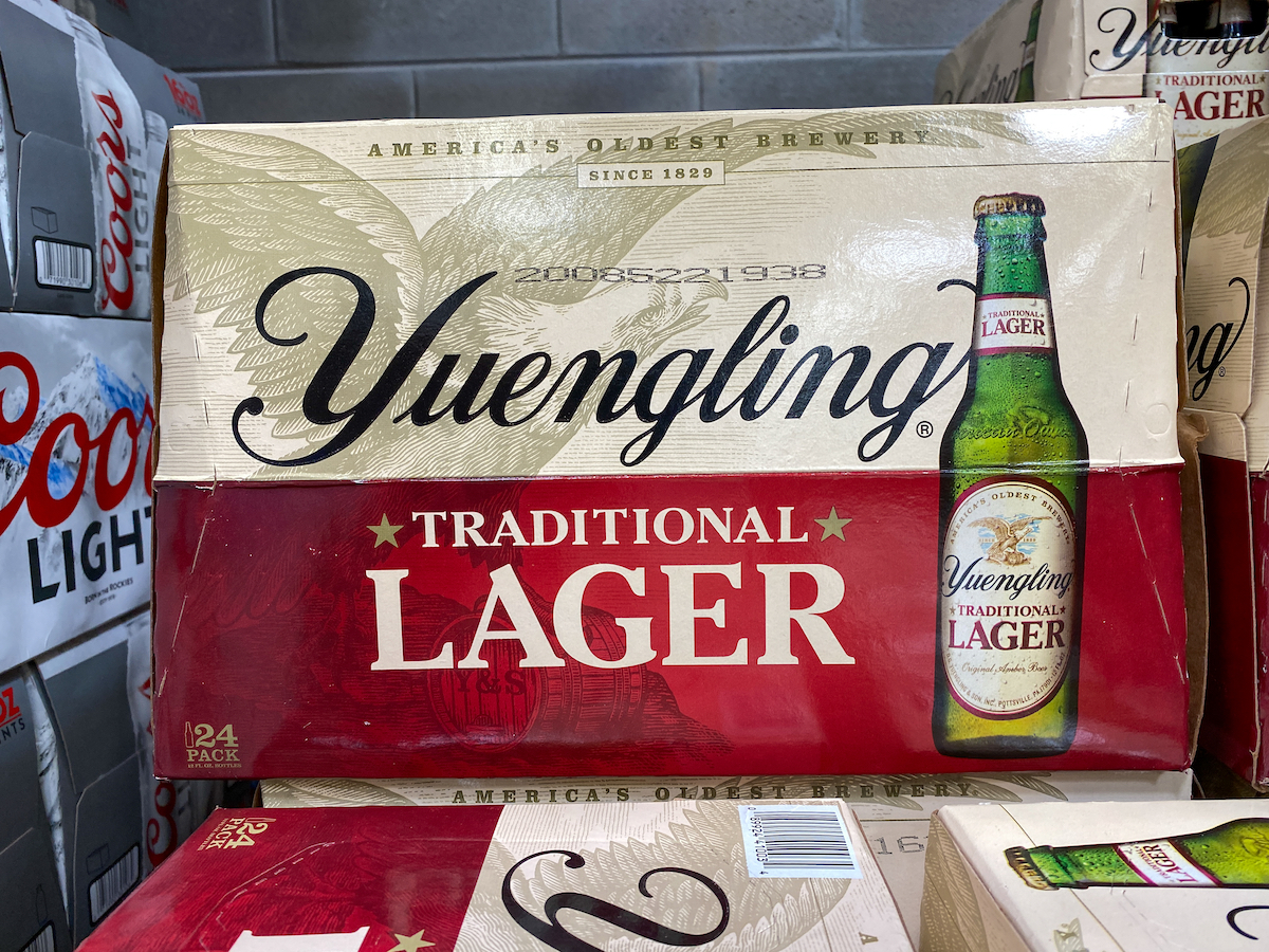 Cases of bottles of Yuengling Traditional Lager at a grocery store waiting for customers to purchase.