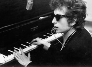 Bob Dylan 1965 at a piano with sunglasses