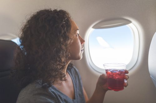woman peacefully looks out an aircraft's window. She is sitting and holding a drink in her left hand.