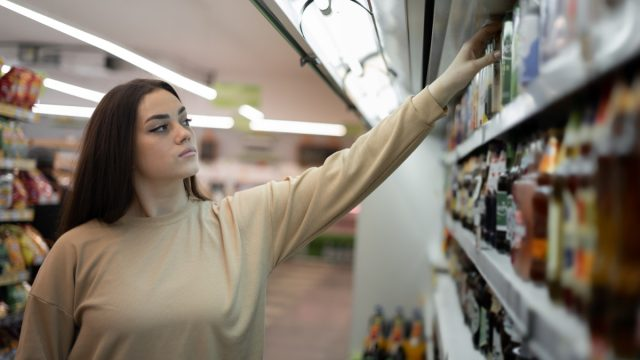 ady stands in a supermarket near a showcase with alcohol