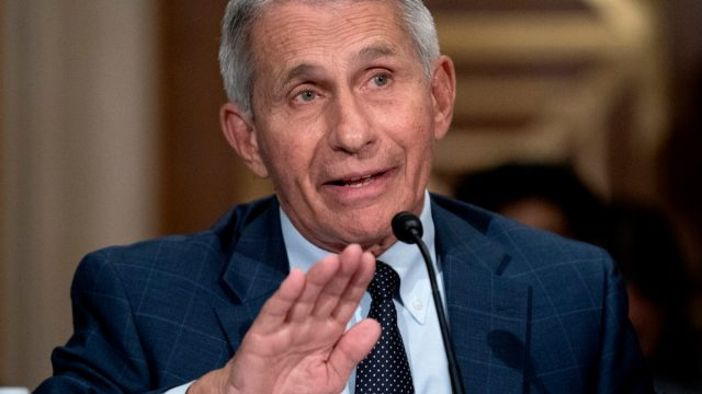 dr anthony fauci raising hand while speaking into a microphone