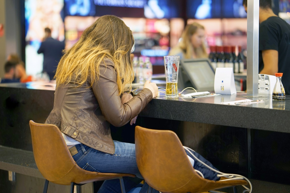 A girl drinks beer in the airport's cafe-bar and waits for her flight. A girl drinks beer in a cafe and looks into the phone.