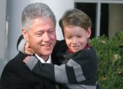 Former U.S. President Bill Clinton, holding his nephew Tyler, smiles after granting a Thanksgiving pardon to a turkey named Jerry, November 22, 2000 in the Rose Garden of the White House.