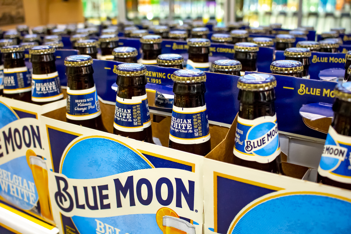Several six pack cases of Blue Moon beer on a shelf at a grocery store