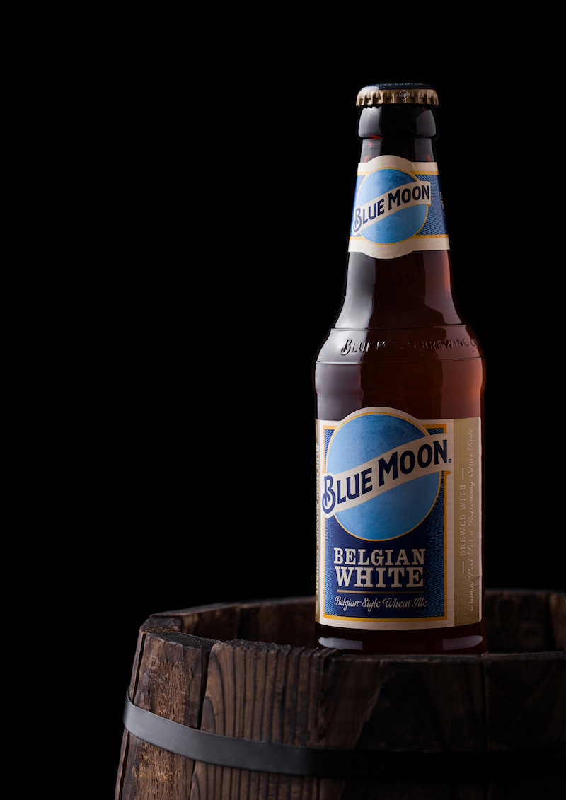 Bottle of Blue Moon belgian white beer, brewed by MillerCoors on old wooden barrel on black background.