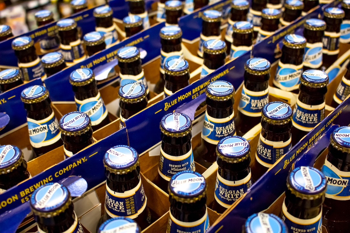 A background full of Blue Moon bottled beer on a shelf at the grocery store