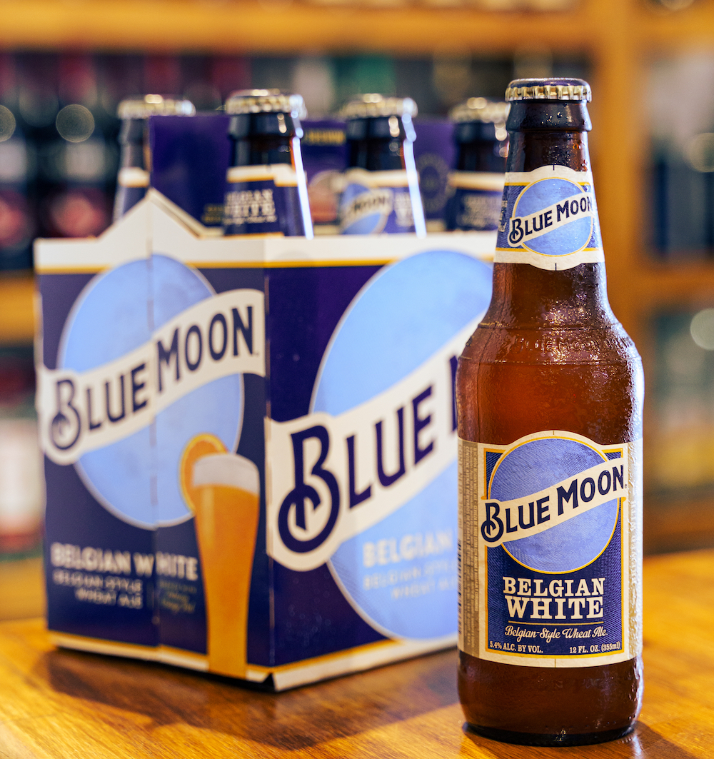 Blue moon beer bottle on wooden bar with out of focus pub background.