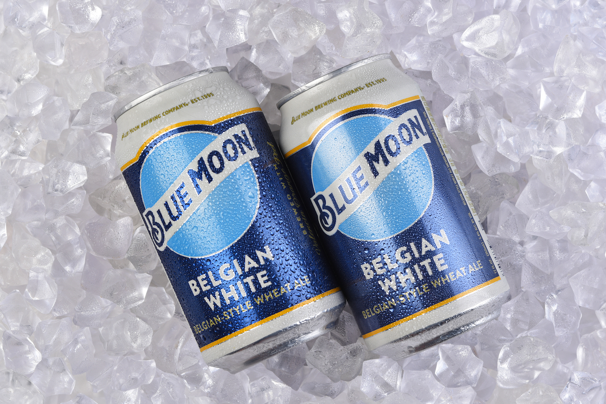 Two cans of Blue Moon Belgian White Ale in a bed of Ice.
