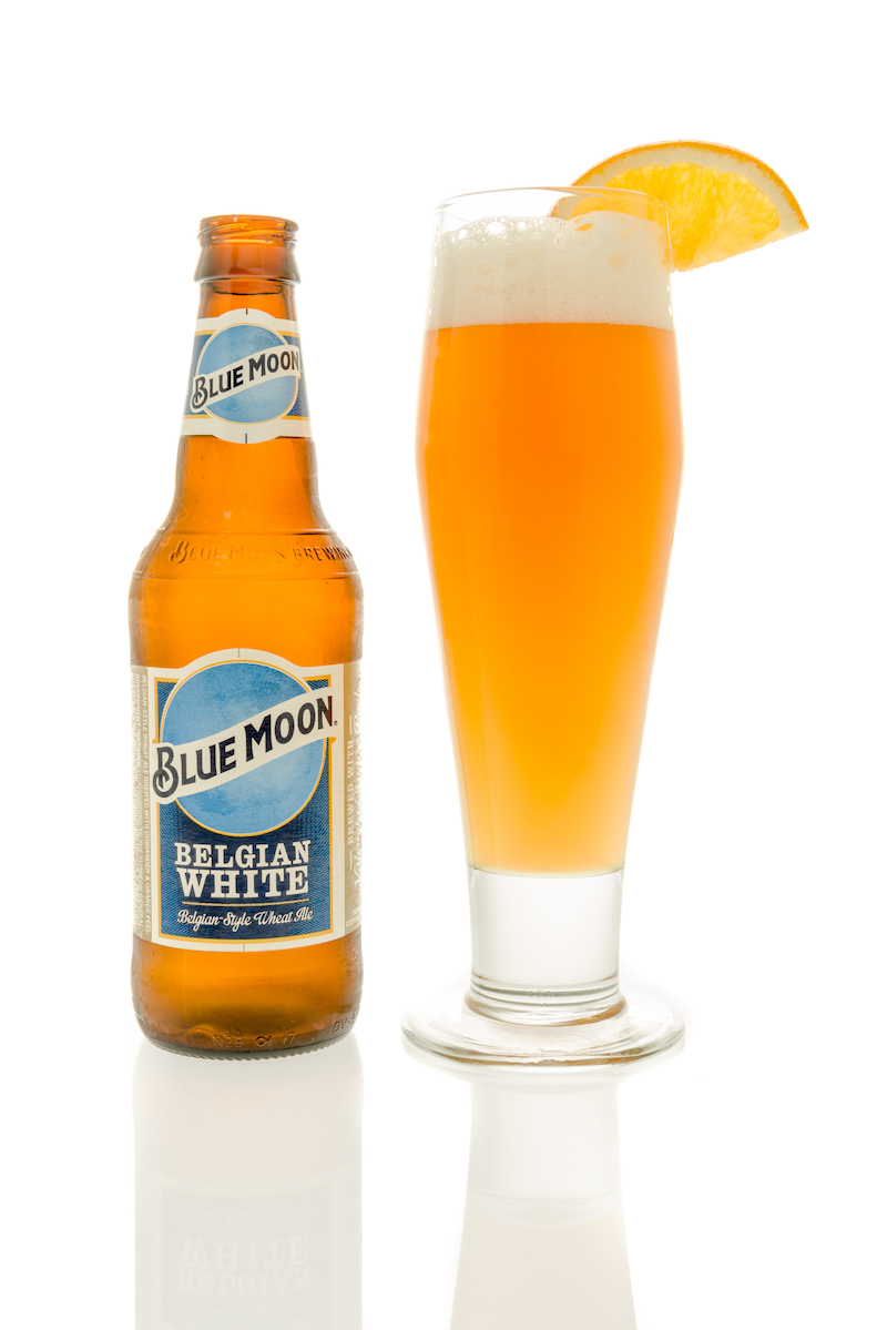 A bottle of Blue Moon beer with a glass and slice of orange on an isolated background.