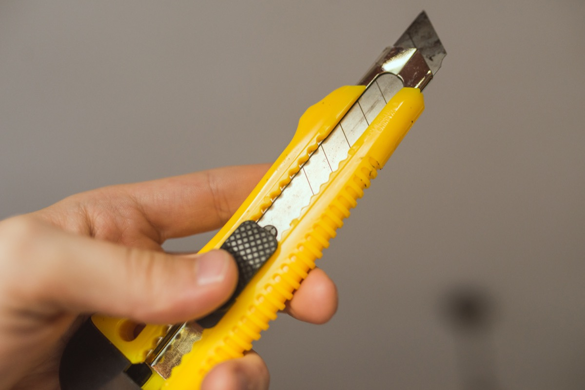 hand holding yellow box cutter tool