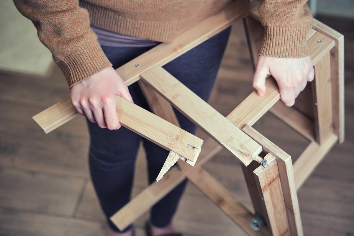 person holding broken chair legs
