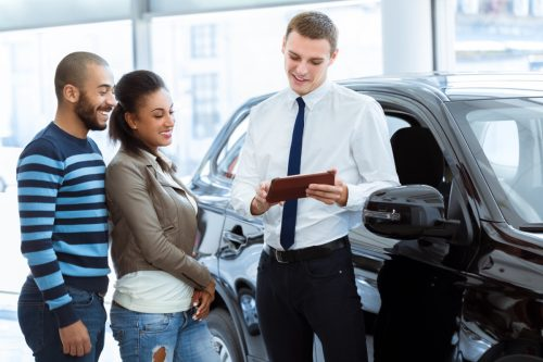 a couple talking to a car salesman at dealership